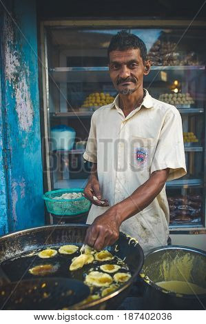 India Maharashtra Vengurla - March 20 2017 Man prepares traditional Indian food in oil.