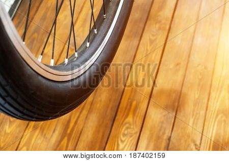 Wheel Of A Stylish Bicycle With A Black Rim And A Black Rubber Tire On A Stylish Wooden Background.
