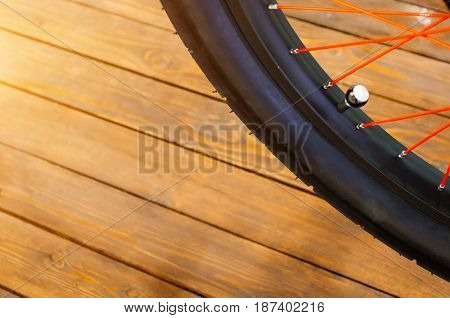 The Wheel Of A Stylish Bicycle With A Black Rim And A Black Rubber Tire, Red Spokes, A Stylish Woode