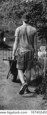 A man carries a primer in a wheelbarrow