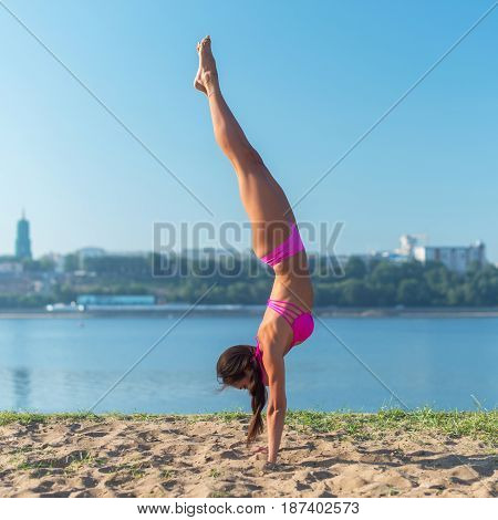 Fit young woman in bikini on beach doing handstand