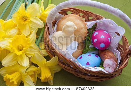 Easter composition - traditional basket with food: pastry colorful eggs meat