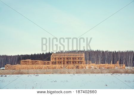 wooden frame ecological house being built. building area outside the city