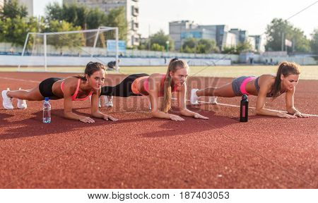 Group of young women doing plank together in stadium.
