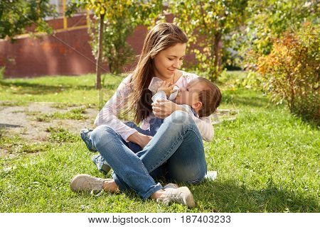 young mother sitting on the grass and feeding her baby from a bottle. Mom and son in a park