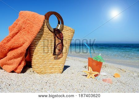 Straw bag beach towel and cocktail on the sand