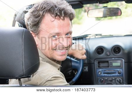 an handsome man in convertible car smiling