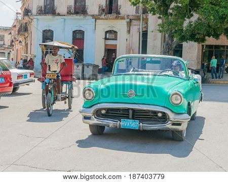 Havana, Cuba - June 30, 2012; Taxi styles on Havana street pedi-cab and green convertible American vintage car moving around city looking for fare.