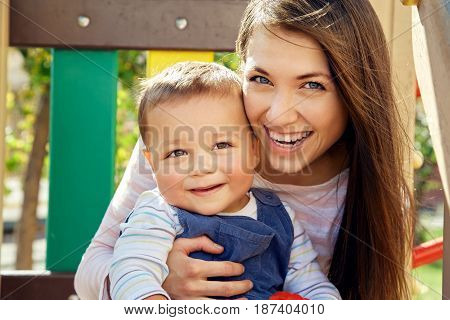 portrait of a young mother with her baby on the playground. Mom and son