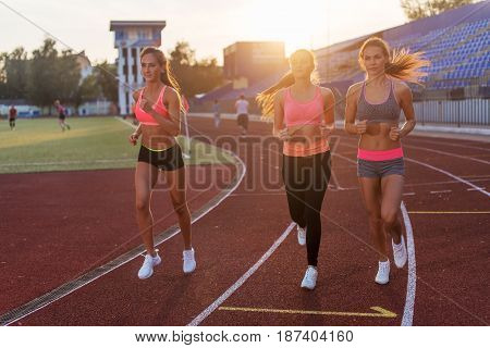 Group of women athletes running together in stadium