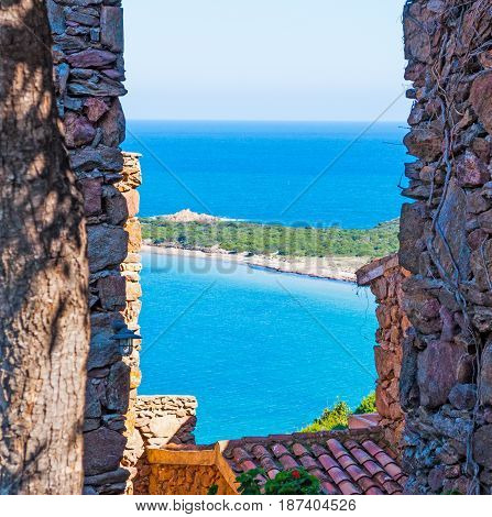 Capo Coda Cavallo shore seen through a rustic wall Sardinia