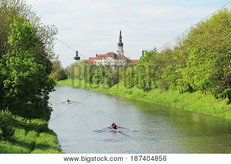people paddling on the boats on Morava river between the banks covered with greenery with beautiful old monastery at the background in Olomouc, Czech Republic, May 10, 2017
