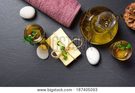 Massage or aromatherapy set: oil stones soap and towel on black stone