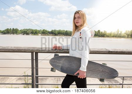 Blonde Girl Near City River With Skateboard