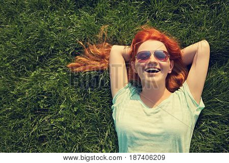relaxing redhead girl lying on the grass. woman in sunglasses relaxation outdoor. photo with artistic effect. vintage toning. film retro style