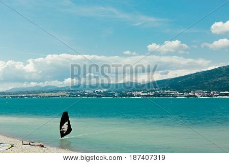 Windsurfer rides to shore along waves of Gelendzhik Bay Vacation Surfing Concept