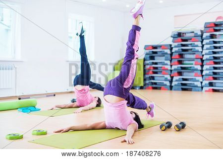 Fit young women stretching body in the fitness studio