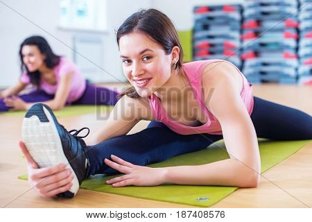 Woman doing cross split exercise working out her hip abductor muscles and ligaments. Fit female athlete stretching splits in gym