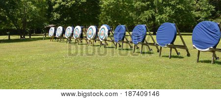 An archery training grounds located in a wooded field. Some of the targets are still covered