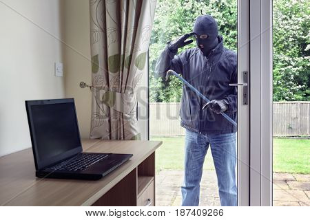 Thief breaking into a house via a patio doors window with a crowbar to steal a laptop computer from an office desk