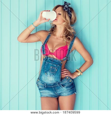 Young sexy woman drinking holding take away coffee cup toned instagram filter.