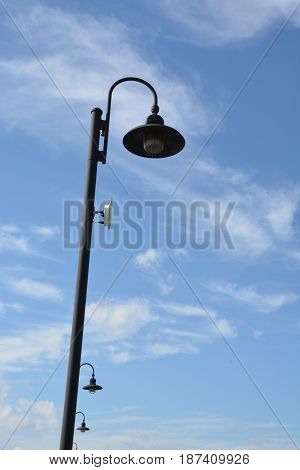 Street light with a curved lighted shown during the day.