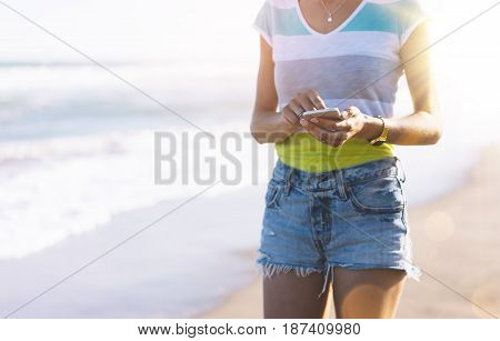 Hipster girl photograph on smart phone gadget in sand coastline mock up of blank screen. Traveler hold and using in female hand mobile on background seascape horizon. Tourist look on blue sun ocean lifestyle