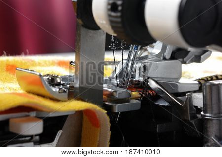 Overlock sewing machine - side view on upper and lower mechanics