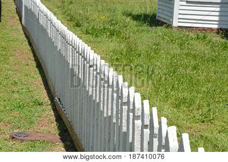 A white picket fence near an old house