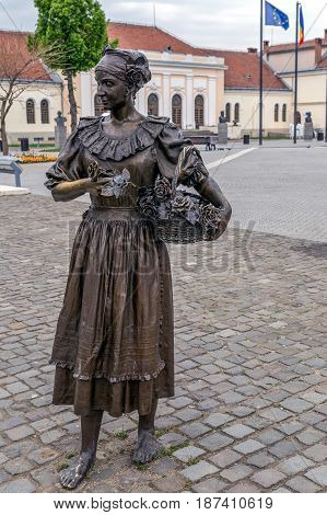 ALBA IULIA ROMANIA - APRIL 29 2017: Bronze statue in Alba Carolina Citadel square depicting a medieval florist woman dressed in frock picking with roses in one flower basket.