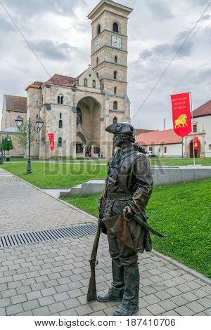 ALBA IULIA Romania - APRIL 29 2017: Bronze statue with soldier in front of catholic cathedral of the City in Citadel of Alba Iulia city. APULUM ROMAN FESTIVAL organized by the City Hall.