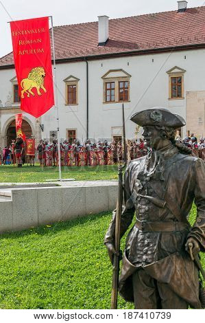 ALBA IULIA Romania - APRIL 29 2017: Bronze statue with soldier in front of one Gate of the City in Citadel of Alba Iulia city. APULUM ROMAN FESTIVAL organized by the City Hall.