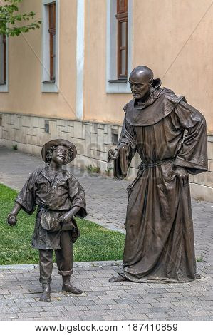 ALBA IULIA ROMANIA - APRIL 29 2017: Group of bronze statues in Alba Carolina Citadel Fortress square depicting an old priest and child on the street symbolizing medieval time.