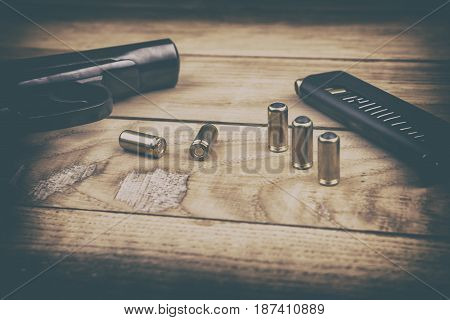 Traumatic pistol with bullets and cartridge on the wooden surface, vintage