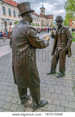 ALBA IULIA ROMANIA - APRIL 29 2017: Bronze statues depicting two town folks with toppers that having a conversation on the street in Alba Carolina Citadel square.