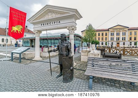 ALBA IULIA ROMANIA - APRIL 30 2017: Bronze statue depicting a Roman legionary holding his spear and shield standing guard at the entrance of the Principia relics Museum in Alba Iulia Citadel square