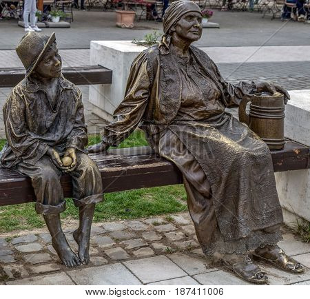 ALBA IULIA ROMANIA - APRIL 29 2017: Group of bronze statues in Alba Carolina Citadel Fortress square depicting one old woman and child on bench symbolizing medieval time.