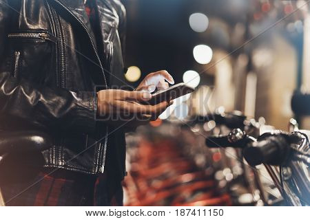 Young girl in black leather jacket using smartphone on background illumination glow bokeh light in night atmospheric christmas city hipster biking and going to work by bicycle on urban street ecology concept
