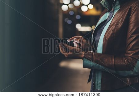 Girl in leather jacket pointing finger on screen smartphone on background illumination glow bokeh light in night atmospheric christmas city hipster using in female hands mobile phone; mockup glitter street