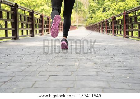 young sport woman running on road in the garden sport and welness concept soft focus
