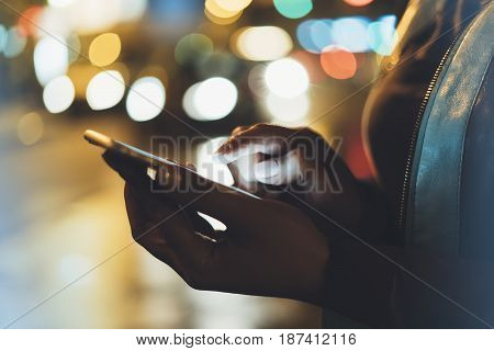 Girl pointing finger on screen smartphone on background illumination glow bokeh light in night atmospheric christmas city hipster using in hands mobile phone headlights auto taxi; mockup glitter street