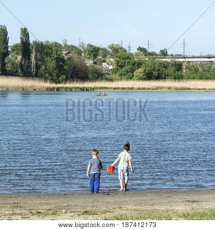 Two boys playing on the banks of the river
