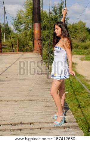 Pretty woman in white sailor costume standing on old wooden bridge