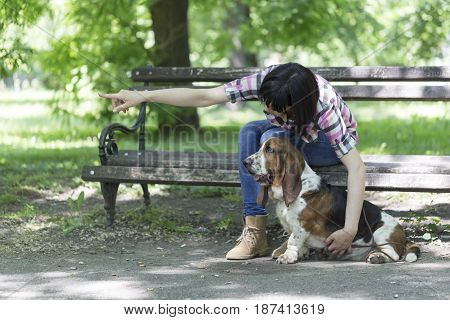 Woman Sits On A Bench In The Park With His Beautiful Dog And Shows Him Which Way To Look.