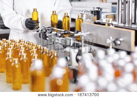 Working Conditions On Factory. Factory Worker Standing Near Belt Conveyor Putting Bottles With Shamp