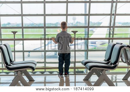 Child 7 Years At The Airport Looking Out The Window, Examining The Plane