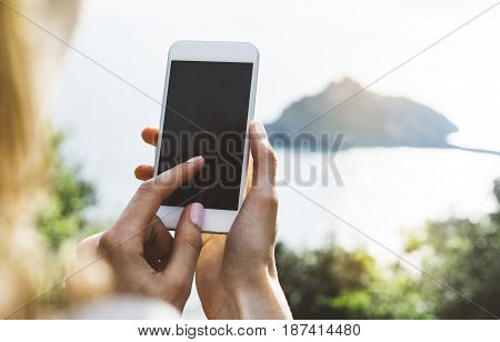 Hipster girl texting message on smartphone mobile closeup view tourist hands using gadget phone in travel on background green mountains and blue sky landscape; finger touch screen cellphone mockup nature templates
