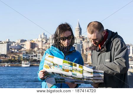 ISTANBUL, TURKEY - 1 APRIL , 2017: Tourists looking at the map in Istanbul amidst the sights