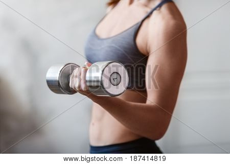 Young athletic woman training hard with dumbells at home. Fitness and healthy lifestyle concept with beautiful sportive caucasian model