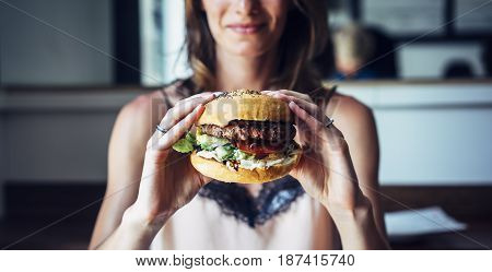 Young girl holding in female hands fast food burger american unhealthy calories meal on background mockup with copy space for text message or design hungry person smiling with grilled hamburger front view